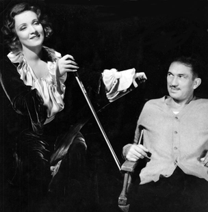 Marlene Dietrich playing the Musical saw - Victor McLaglen listening